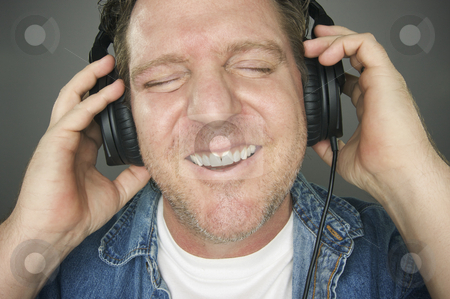 Man Wearing Headphones stock photo, Man with Eyes Shut Wearing Headphones Enjoying His Music on a Grey Background. by Andy Dean