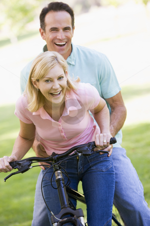 Couple on one bike outdoors smiling stock photo,  by Monkey Business Images