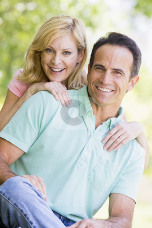 Couple outdoors smiling stock photo,  by Monkey Business Images