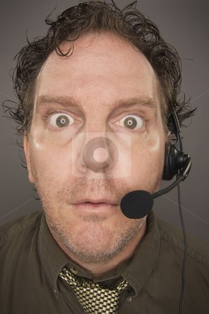 Stunned Businessman stock photo, Stunned Businessman Wearing Phone Headset Against a Grey Background. by Andy Dean