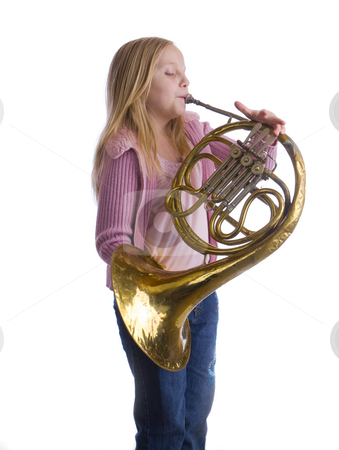 Girl Playing Horn stock photo, Girl playing an old French horn while standing by John McLaird