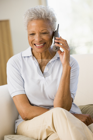 Woman sitting in living room using telephone and smiling stock photo,  by Monkey Business Images