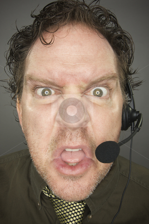 Irate Businessman stock photo, Irate Businessman Wearing a Phone Headset Against a Grey Background. by Andy Dean