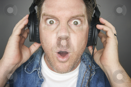 Shocked Man Wearing Headphones stock photo, Shocked Man Wearing Headphones against a grey background. by Andy Dean