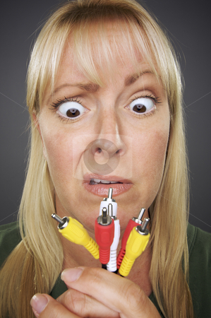 Confused Woman Holding Electronic Cables stock photo, Confused Woman Holding Electronic Cables Against a Grey Background. by Andy Dean
