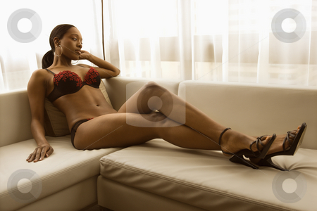 Woman in lingerie. stock photo, Young African American woman reclining on couch in lingerie and heels. by Iofoto Images