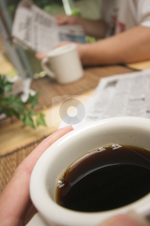 Morning Coffee stock photo, Morning Coffee Macro of Cup with man reading newspaper in background. by Andy Dean