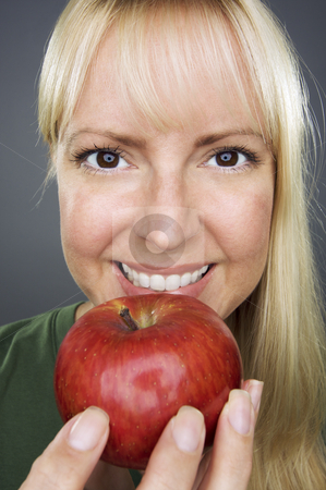 Beautiful Woman With Apple stock photo, Beautiful Woman With Apple Against A Grey Background by Andy Dean