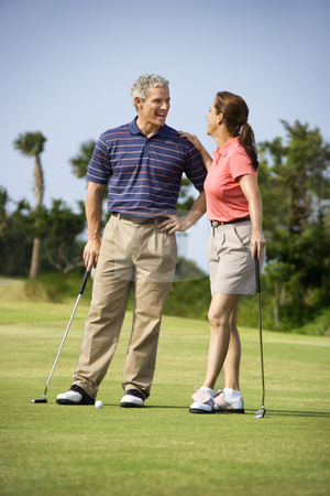 Couple talking on golf course stock photo, Caucasion mid-adult man and woman standing on golf course talking to each other. by Iofoto Images