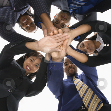 Business teamwork. stock photo, Low angle portrait  of multi-ethnic business group of men and women with hands in huddle. by Iofoto Images