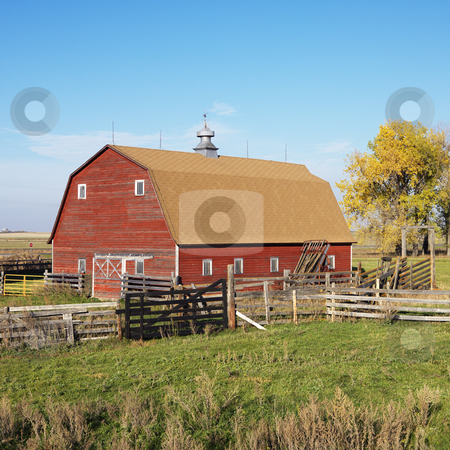 Red barn and fence. stock photo, Red barn and fence in field. by Iofoto Images