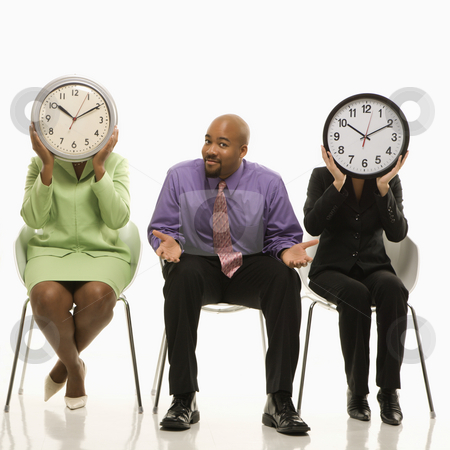 Work time concept. stock photo, Businesswomen sitting holding clocks over faces while African-American businessman shrugs. by Iofoto Images