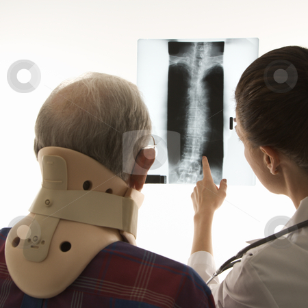Doctor and injured patient. stock photo, Over the shoulders view of mid-adult Caucasian female pointing at an x-ray as elderly Caucasian male in neck brace looks on. by Iofoto Images