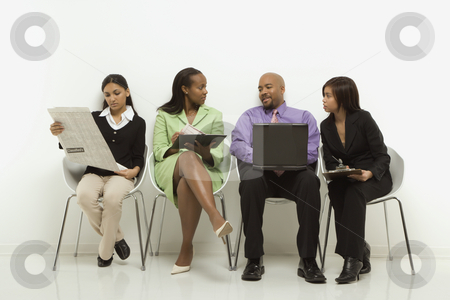 Business group. stock photo, Multi-ethnic business group of men and women sitting looking at laptop and papers. by Iofoto Images