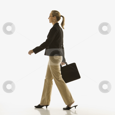 Businesswoman with briefcase. stock photo, Mid-adult Caucasian businesswoman walking and carrying briefcase. by Iofoto Images