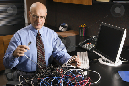 Businessman with computer. stock photo, Caucasian middle-aged businessman at desk in office with a tangle of computer cables. by Iofoto Images