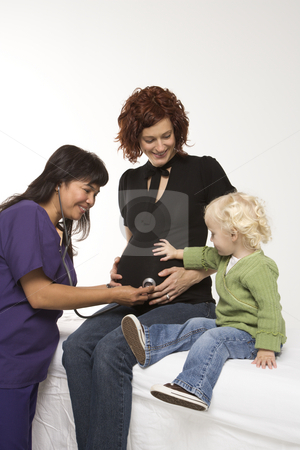 Pregnant woman having exam. stock photo, Nurse holding stethoscope on Caucasian pregnant woman's belly as daughter holds hand on belly. by Iofoto Images