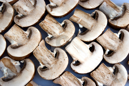 In a row stock photo, A group of sliced mushrooms laid out on a chopping board by Paul Phillips