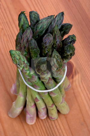 Bundle of asparagus stock photo, A bundle of asparagus tied up on a wooden work surface by Paul Phillips