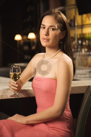 Woman drinking wine. stock photo, Mid adult Caucasian woman sitting at bar with glass of white wine looking at viewer. by Iofoto Images