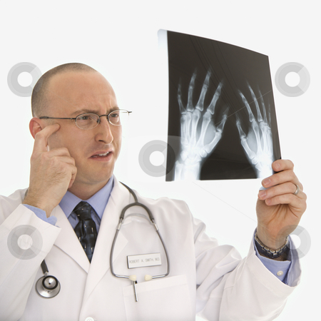 Doctor looking at xrays. stock photo, Caucasian mid adult male physician holding up hand xrays looking perplexed. by Iofoto Images