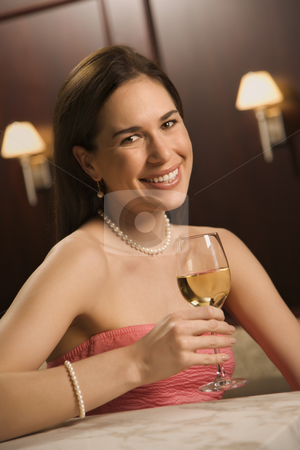 Woman drinking wine. stock photo, Mid adult Caucasian woman sitting at bar drinking glass of white wine and smiling. by Iofoto Images