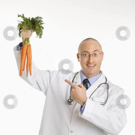 Doctor holding carrots. stock photo, Caucasian mid adult male physician holding and pointing to bunch of carrots. by Iofoto Images