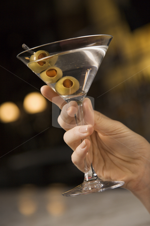 Woman holding martini. stock photo, Mid adult female Caucasian hand holding a martini with three olives. by Iofoto Images