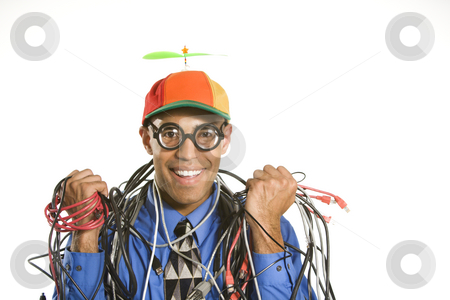 Man wrapped in cables. stock photo, African American businessman wrapped in computer cables wearing nerd hat and glasses. by Iofoto Images