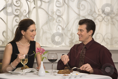 Couple dining at restaurant. stock photo, Mid adult Caucasian couple smiling eating in restaurant. by Iofoto Images