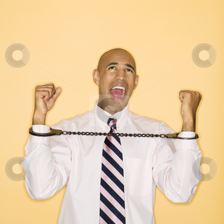 Man in handcuffs. stock photo, African American man wearing handcuffs and screaming. by Iofoto Images