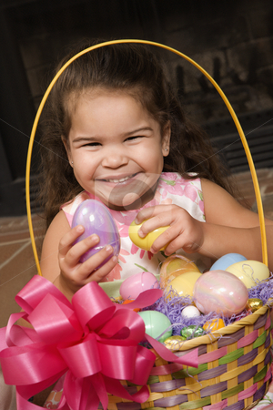 Girl with Easter basket. stock photo, Hispanic girl holding egg from Easter basket looking at viewer smiling. by Iofoto Images