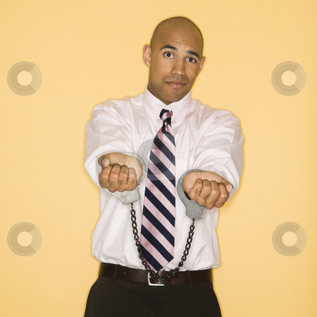 Man in handcuffs. stock photo, African American man wearing handcuffs and looking sad. by Iofoto Images