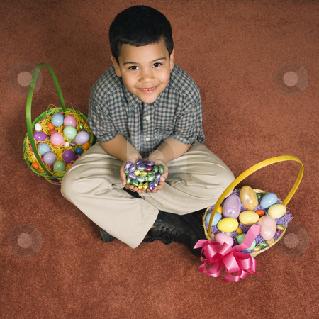 Boy with Easter baskets. stock photo, Hispanic boy sitting on floor with two Easter baskets holding chocolate candy eggs in his hands looking up at viewer smiling. by Iofoto Images