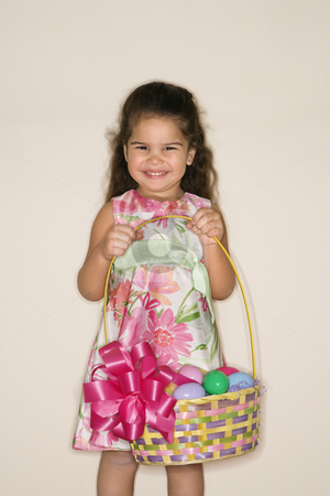 Girl holding Easter basket. stock photo, Hispanic girl holding Easter basket smiling and looking at viewer. by Iofoto Images