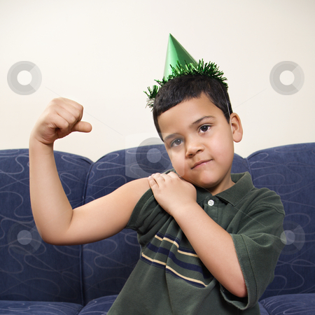 Hispanic boy wearing party hat playfully flexing arm muscle while looking at viewer. Add to lightbox
