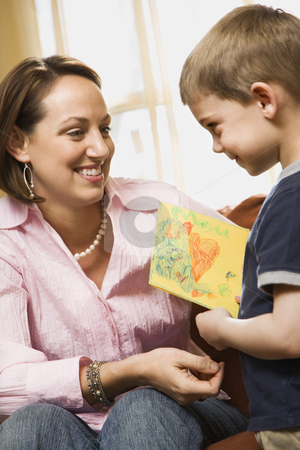 Boy giving mom drawing. stock photo, Caucasian boy giving mid adult mother a drawing. by Iofoto Images