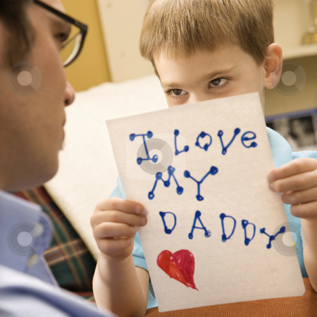 Boy giving dad drawing. stock photo, Caucasian boy giving mid adult father a drawing. by Iofoto Images
