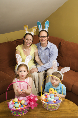 Family at Easter. stock photo, Caucasian family wearing rabbit ears with Easter baskets looking at viewer. by Iofoto Images