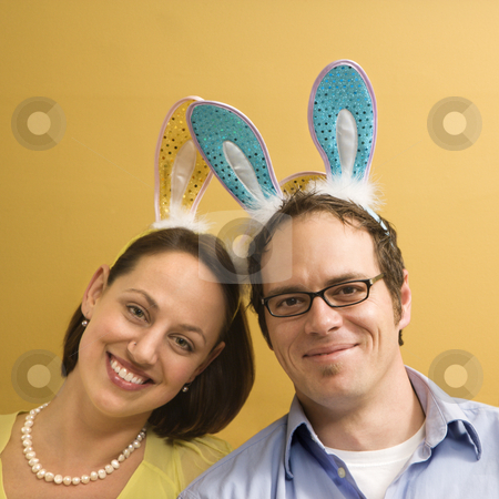 Couple wearing rabbit ears. stock photo, Caucasian mid adult couple wearing rabbit ears and looking at viewer. by Iofoto Images
