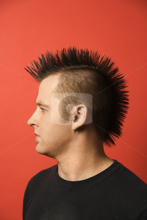 Man with mohawk. stock photo, Profile portrait of Caucasian man with spiked mohawk against orange background. by Iofoto Images