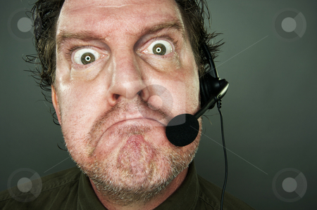 Bad Day At Work? stock photo, Frowning man with telephone headset. by Andy Dean
