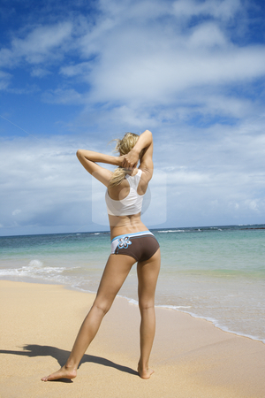 Woman stretching on beach. stock photo, Caucasian young adult woman stretching on beach. by Iofoto Images
