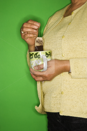 Woman dipping tea bag. stock photo, African American female mature adult dipping tea bag in mug. by Iofoto Images