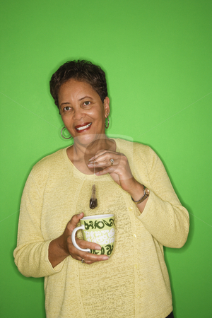 Woman making hot tea. stock photo, African American female mature adult dipping tea bag in mug. by Iofoto Images