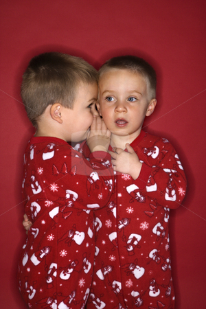 Boy twin brothers whispering. stock photo, Young male twin child whispering to other twin. by Iofoto Images