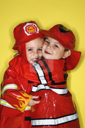 Twin boys dressed as firemen. stock photo, Caucasian twin boys dressed as firemen hugging against yellow background. by Iofoto Images