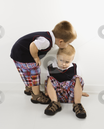 Boy kissing brother on head. stock photo, Caucasian twin boy kissing other twin boy on head. by Iofoto Images