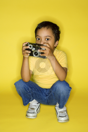 Male child kneeling with camera. stock photo, Hispanic male child kneeling with camera. by Iofoto Images