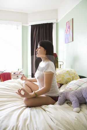 Young woman meditating. stock photo, Side view of pretty  Asian young woman sitting on bed in underwear and t-shirt meditating in lotus pose. by Iofoto Images